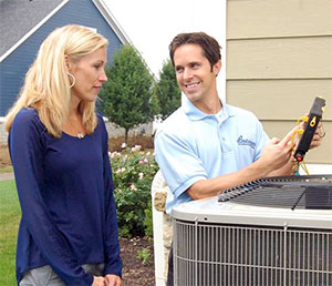 Woman standing with technician next to an AC unit