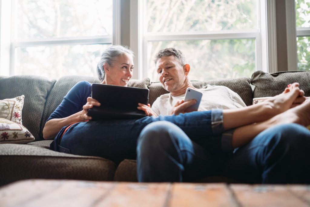 A couple in their 50's relax in their home on the living room couch, enjoying reading and surfing the internet on their mobile touchscreen phones and computer tablet.