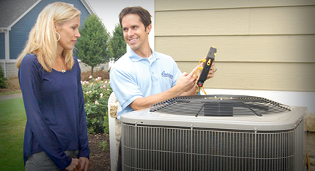 A technician speaking with a customer near an outdoor AC unit